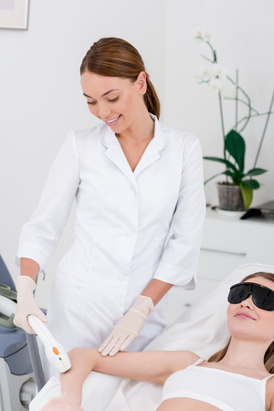 woman receiving laser hair removal procedure on arm made by cosmetologist in salon