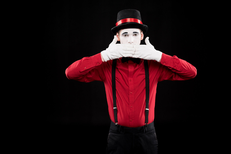 mime covering mouth with hands isolated on black