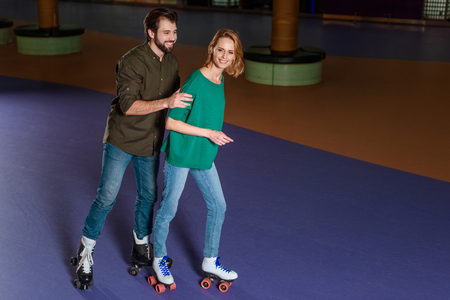 young smiling couple skating together on roller rink Stock Photo