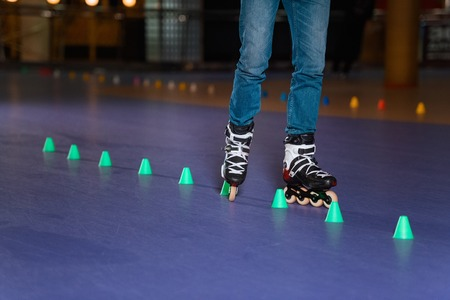 partial view of man in roller skates skating on roller rink with cones