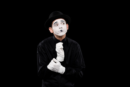 pensive mime looking away isolated on black