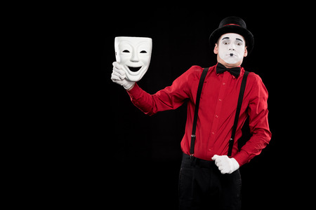 scared mime holding white mask isolated on black