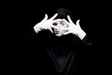 mime looking at camera through spread fingers isolated on black Archivio Fotografico