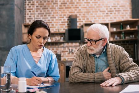 Female nurse writing down senior patient medical complaints