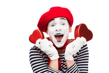 happy mime holding heart shaped gift boxes isolated on white, st valentines day concept