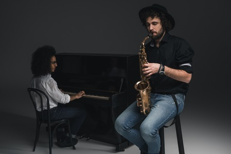 man playing saxophone while his partner playing piano blurred on background Stock Photo