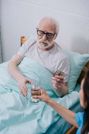 Nurse giving a glass of water to patient with pills Stock Photo