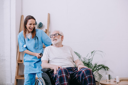 Laughing nurse and senior patient in wheelchair