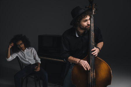 man playing violoncello while his depressed partner sitting at piano blurred on background Stock Photo
