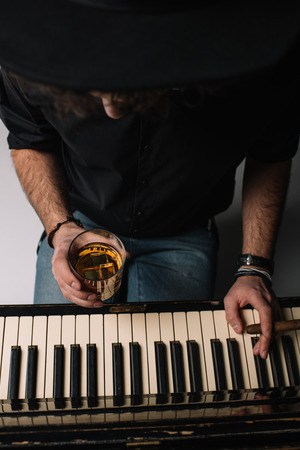 high angle view of musician with glass of whiskey and cigar playing piano 写真素材 - 111232191