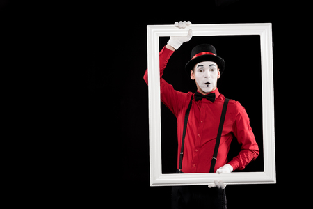 surprised mime holding frame isolated on black