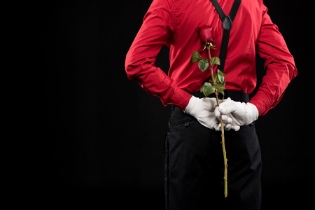 cropped image of mime hiding rose behind back isolated on black Banque d'images - 111234329