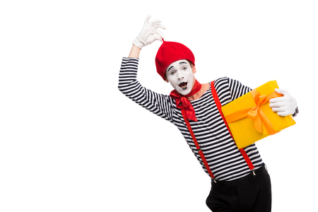 surprised mime holding gift box and touching red cap isolated on white