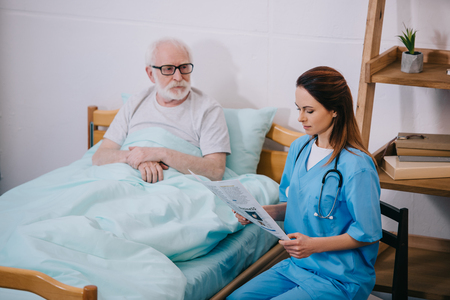 Old man patient looking at nurse reading newspaper
