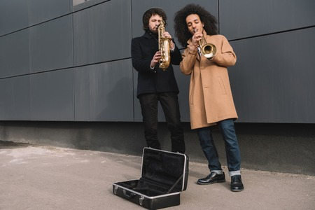 duet of street musicians playing trumpet and saxophone outdoors