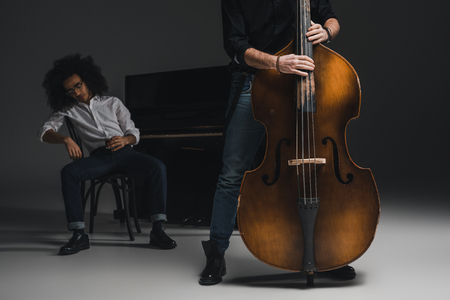 cropped shot of man playing violoncello while his depressed partner sitting at piano blurred on background