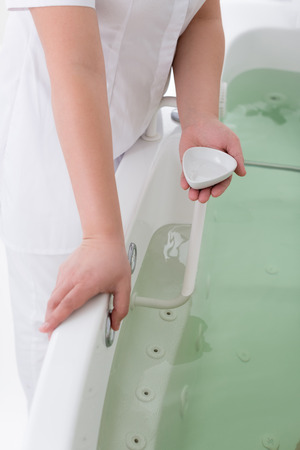 cropped shot of spa salon assistant standing near hydro bath