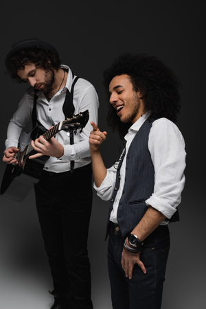 young duet of musicians playing guitar and singing on black