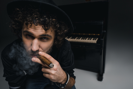 close-up portrait of young musician smoking cigar in front of piano and looking at camera