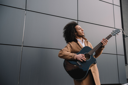 african american street musician playing guitar outdoors Stock Photo