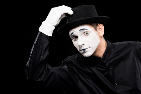 mime greeting and touching hat isolated on black Фото со стока