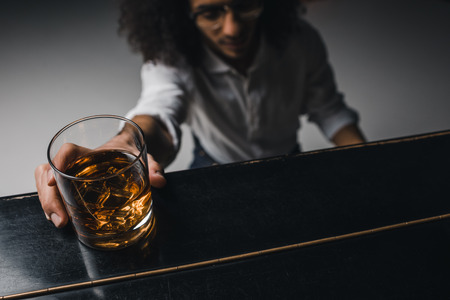 young man playing piano and reaching for glass of whiskey 写真素材