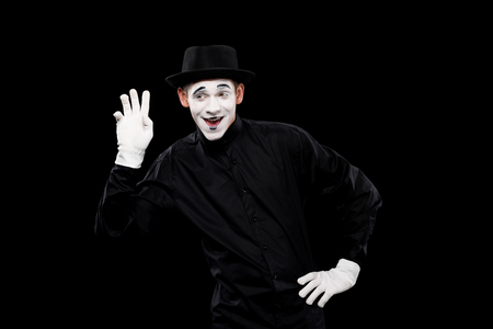 happy mime waving hand isolated on black