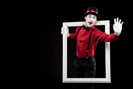 gelukkige mime zwaaiende hand van frame geïsoleerd op zwart