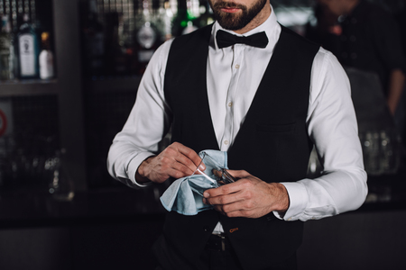 cropped image of male bartender cleaning glass with rag in evening