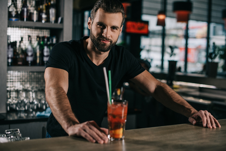 handsome barman standing with alcohol drink at bar counter