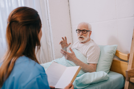 Old man patient and nurse discussing plot of the book Zdjęcie Seryjne
