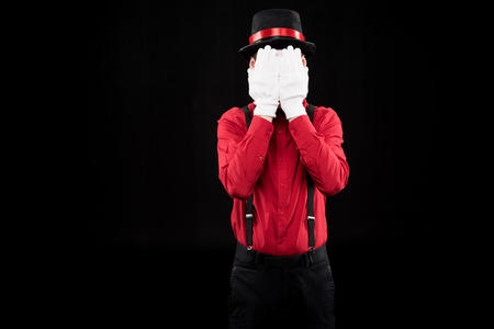 mime covering face with hands isolated on black Stock Photo
