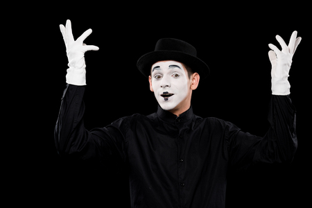 mime showing hands and looking at camera isolated on black