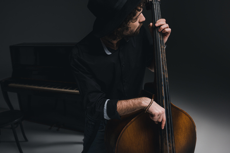 young handsome musician playing contrabass