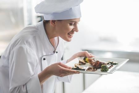 attractive chef sniffing cooked steak at restaurant kitchen Imagens