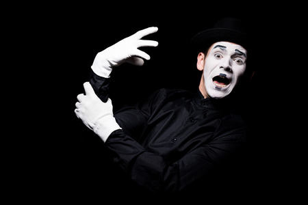 scared mime with hand monster looking at camera isolated on black Archivio Fotografico