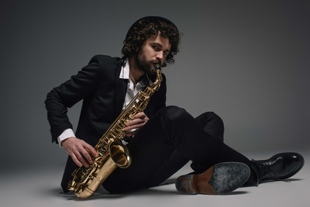 bearded jazzman playing saxophone while sitting on floor