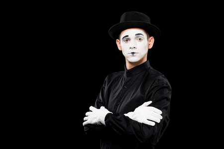 mime standing with crossed arms and looking at camera isolated on black