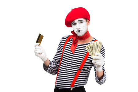 sad mime holding credit card and cash isolated on white Stock Photo