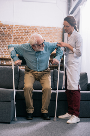Doctor helping senior patient with crutches
