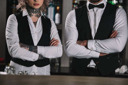 cropped image of female and male bartenders standing with crossed arms at bar