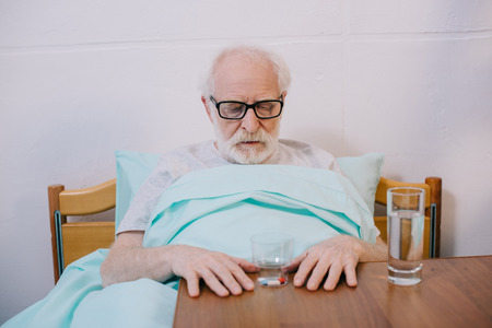 Senior man patient in clinical bed looking at his medications