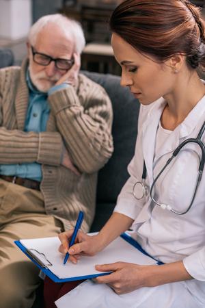 Female doctor writing down senior patient medical complaints Foto de archivo - 111279232