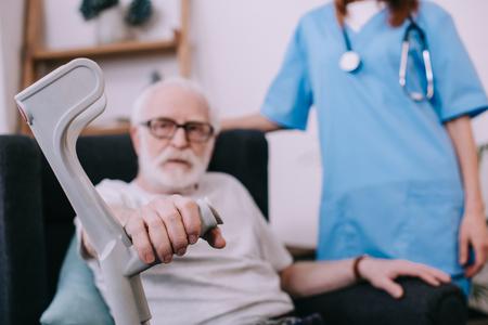 Nurse standing behind senior man with crutch