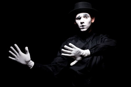mime pretending touching something isolated on black Stock Photo