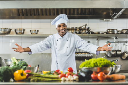 handsome african american chef standing with open arms at restaurant kitchen Фото со стока