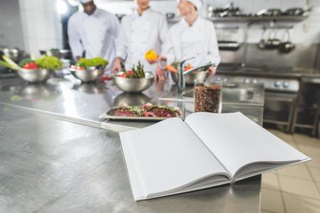 multiethnic chefs at restaurant kitchen with recipe book on foreground