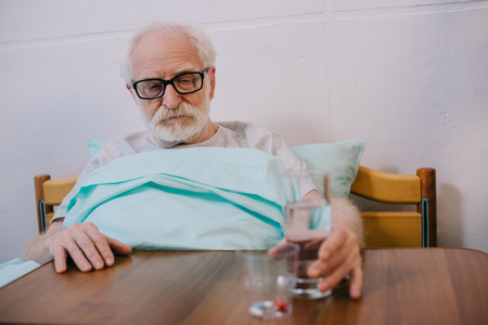 Senior man patient in clinical bed taking medications