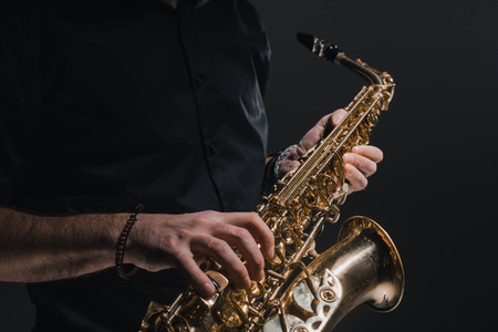 cropped shot of man playing saxophone on black Standard-Bild