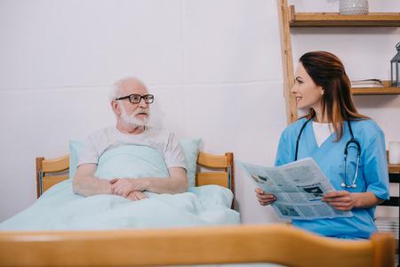 Nurse reading newspaper to senior patient